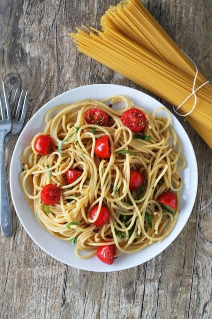tomato, basil and garlic brown butter pasta in a bowl with a bunch of dried spaghetti noodles in the background