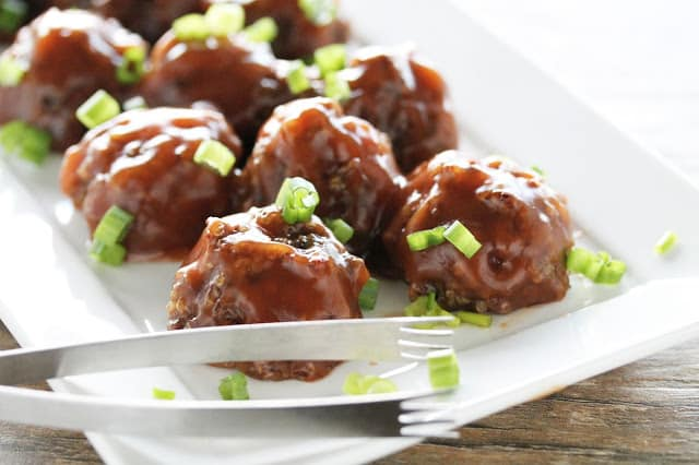 Vegan sweet and sour meatballs on a white serving platter with tongs