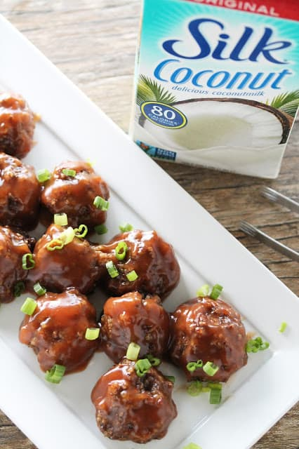 Vegan sweet and sour meatballs on a white serving platter with Silk coconut milk in background
