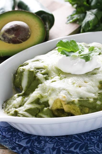 Mole Verde Chicken Enchiladas are stuffed with flavorful chicken and avocado, then smothered in a delicious green mole sauce.