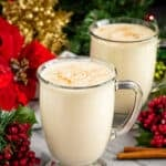 Homemade Eggnog in two mugs surrounded by christmas decorations