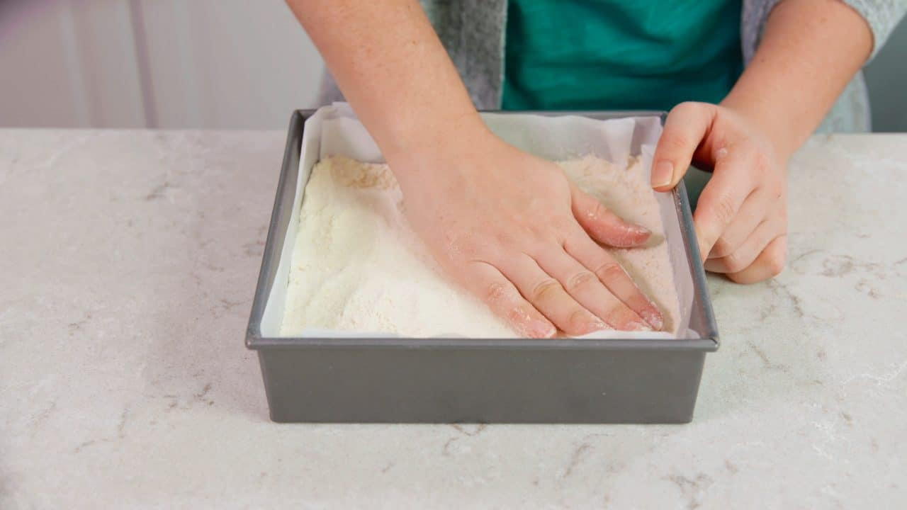 Shortbread crust being placed into a pan.