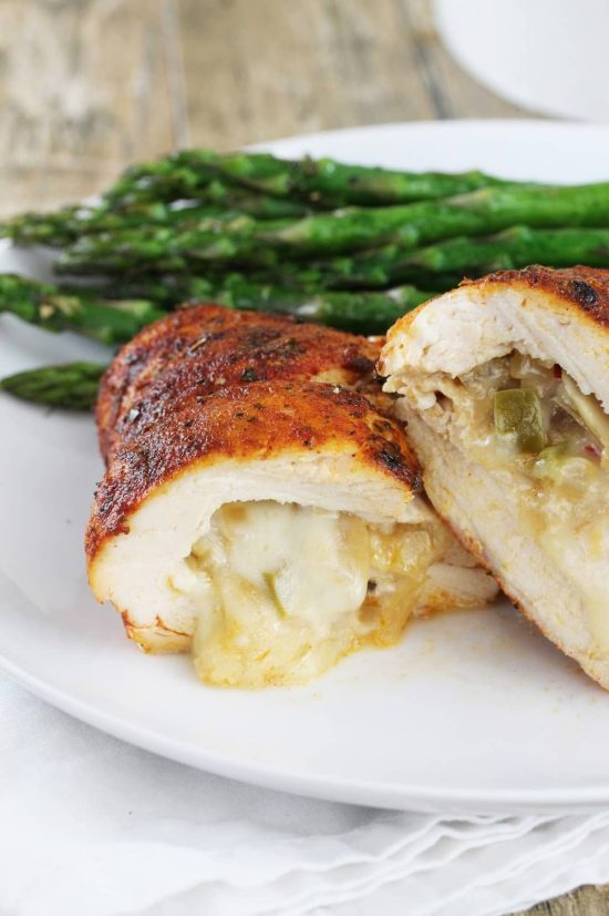 Cajun-spiced chicken breasts stuffed with bell peppers, mushrooms, and onions and zesty pepperjack cheese on a plate with asparagus