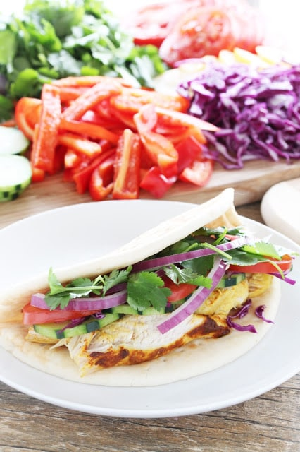 Moroccan-spiced chicken breasts sliced and served gyro style with tons of vegetables and topped off with a zingy tahini sauce.