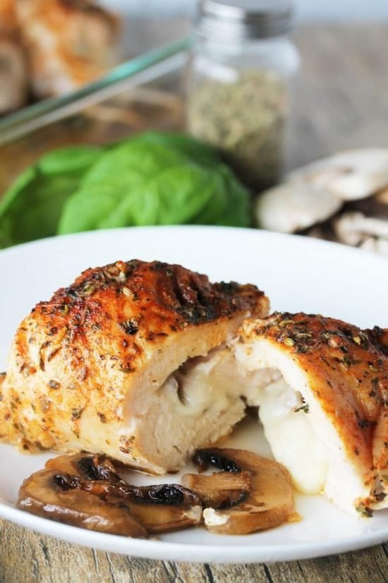 Stuffed herb chicken breast sliced in have on a white plate with sauted mushrooms
