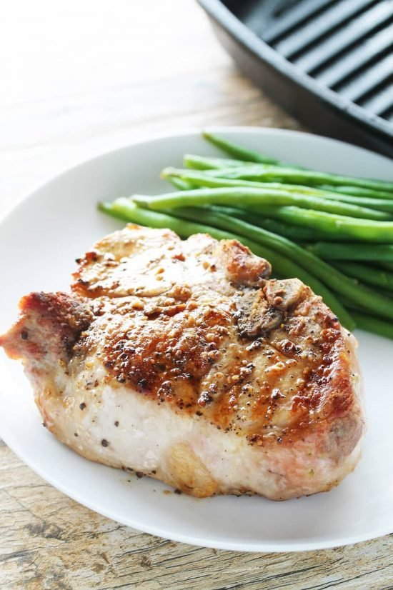 Thick cut juicy bone-in pork chop with a side of green beans