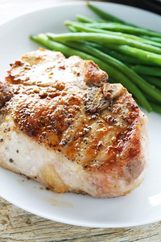Close-up of a think cut, bone-in juicy grilled pork chop on a plate with green beans
