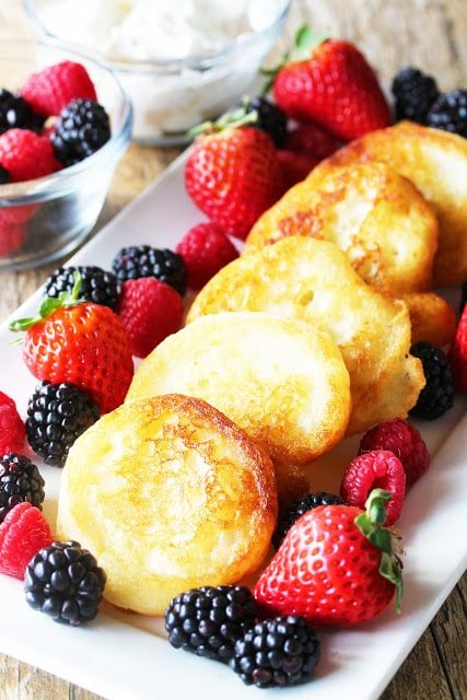 Fried pancakes on a white plate with blackberries and strawberries.