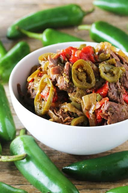 Slow cooked jalapeno beef in a white bowl surrounded by jalapeno peppers.