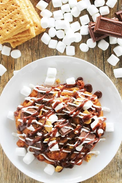 Bird's eye view of Graham Cracker flavored funnel cake topped with pieces of milk chocolate and mini marshmallows, then drizzled with homemade marshmallow sauce and homemade chocolate sauce
