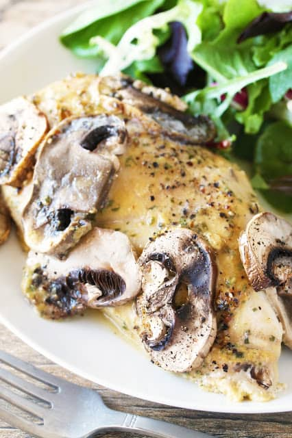 Mushroom covered baked chicken covered in honey-dijon sauce with greens