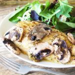 A Baked Honey-Dijon Chicken chicken breast seasoned with tarragon and topped with sliced mushrooms, served with a salad on a plate