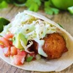 Crispy battered cod is topped with avocado salsa, simple slaw and jalapeno, wrapped in a corn tortilla and served with a lime wedge