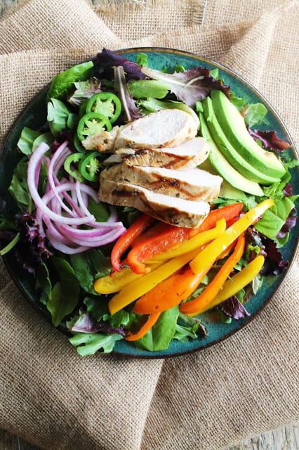 Grilled Mojo Chicken Salad served up with slices of avocado and jalapeno, grilled bell peppers, and pickled red onion over a bed of lettuce.