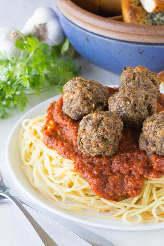Baked meatballs with homemade spaghetti sauce on a plate of spaghetti