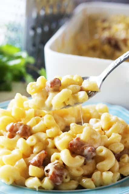 A fork lifts a bite of the cheesy goodness of Gourmet Pork Belly Mac and Cheese