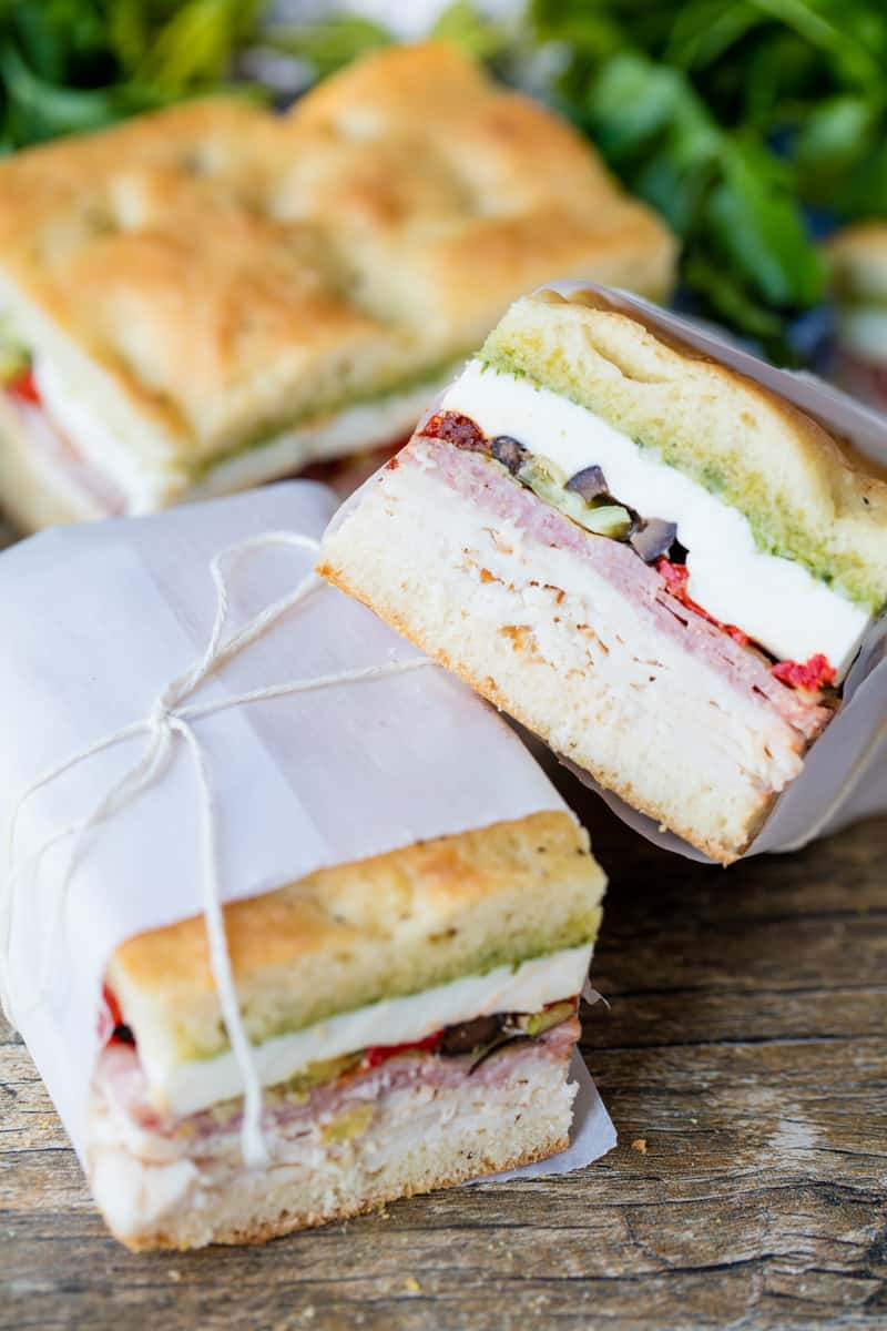 Pressed Italian Sandwich made of sliced chicken breast, sliced salami, sundried tomatoes, olives, pepperocinis, red bell peppers, and fresh mozzarella with a pesto sauce wrapped in wax paper.