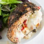 Italian Stuffed Chicken: Balsamic and herb glazed chicken, stuffed with artichoke, bell pepper, and fennel and oozing with melted mozzarella, served with a salad on a plate.