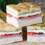 A stack of three Pressed Italian Sandwichs made of sliced chicken breast, sliced salami, sundried tomatoes, olives, pepperocinis, red bell peppers, and fresh mozzarella with a pesto sauce.