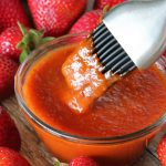 A basting brush dips into a bowl of Strawberry Chipotle BBQ Sauce