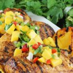 Chipotle-Peach Glazed Grilled chicken breasts on a plate is topped with peach salsa, cilantro in background