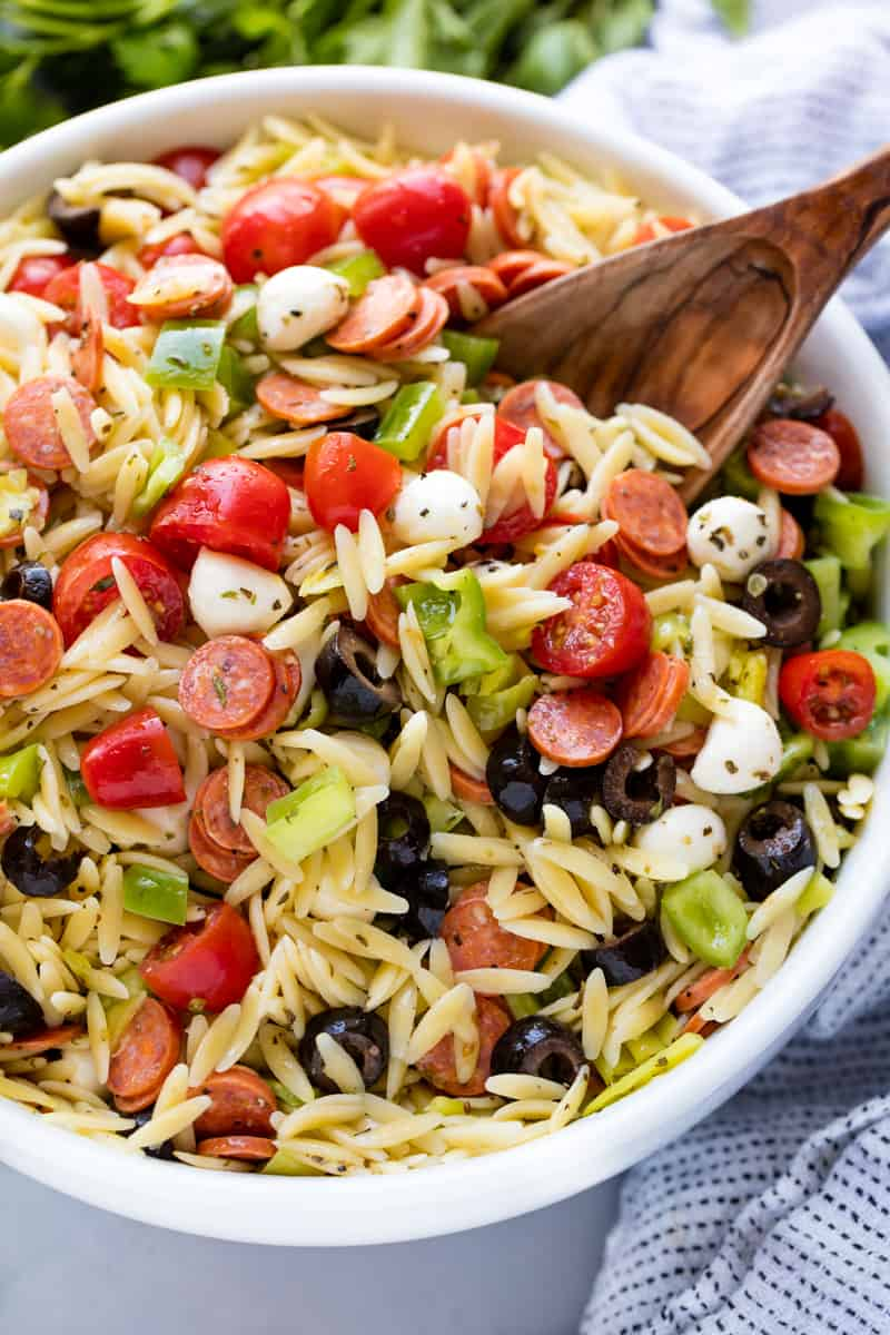 Italian Pasta Salad in a white bowl with a wooden spoon in it.