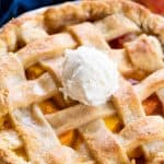 Peach Pie in a ceramic pie pan topped with a scoop of ice cream.