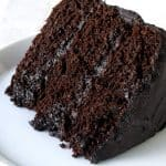 A slice of Moist Chocolate Cake layered with chocolate frosting with a bite taken out with a fork