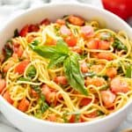 Tomato Pasta in a white bowl topped with basil.