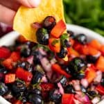 A chip dips into a bowl of Blueberry Bell Pepper Salsa