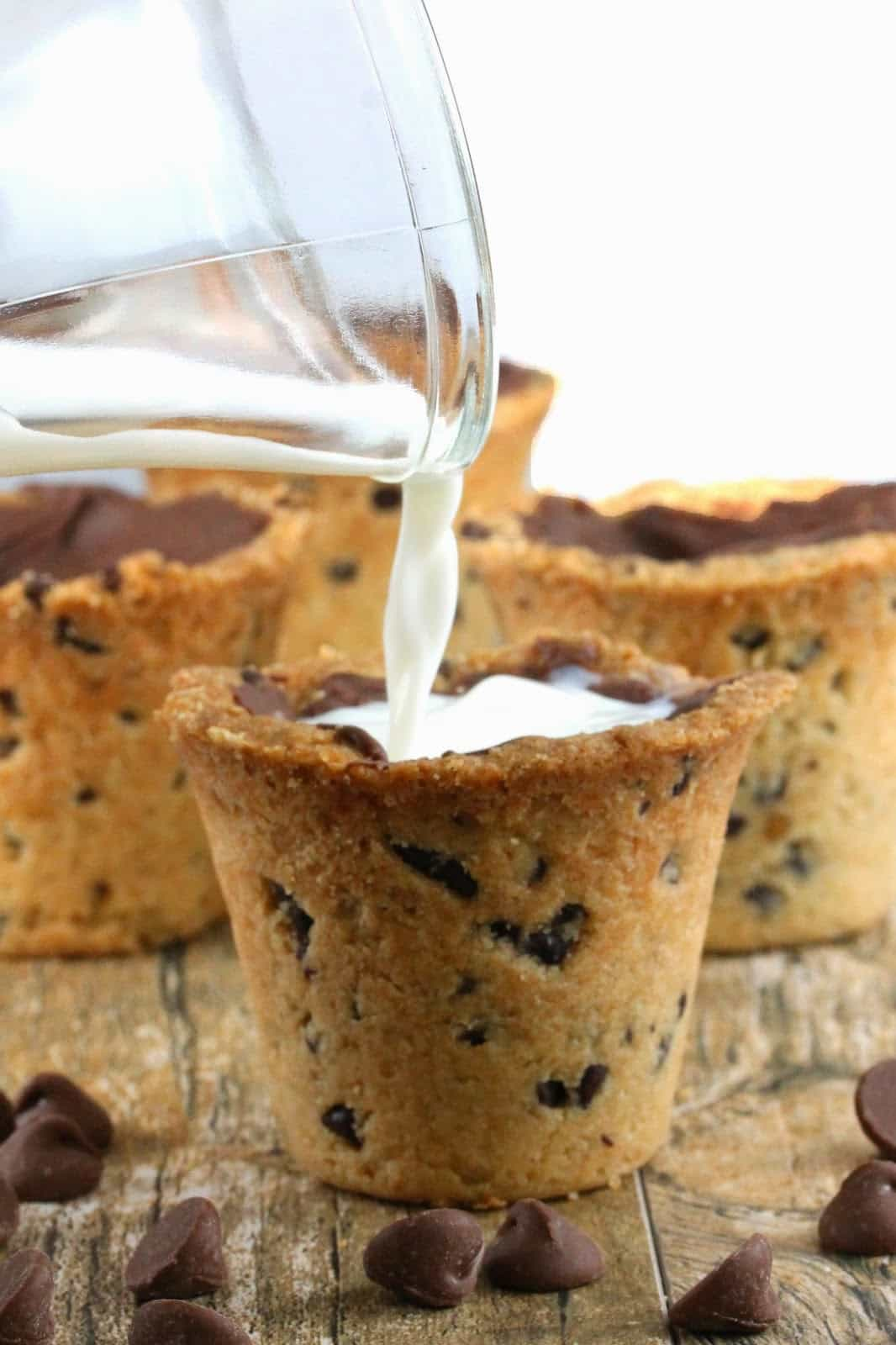 Chocolate chip cookie shot cup getting milk poured into it.