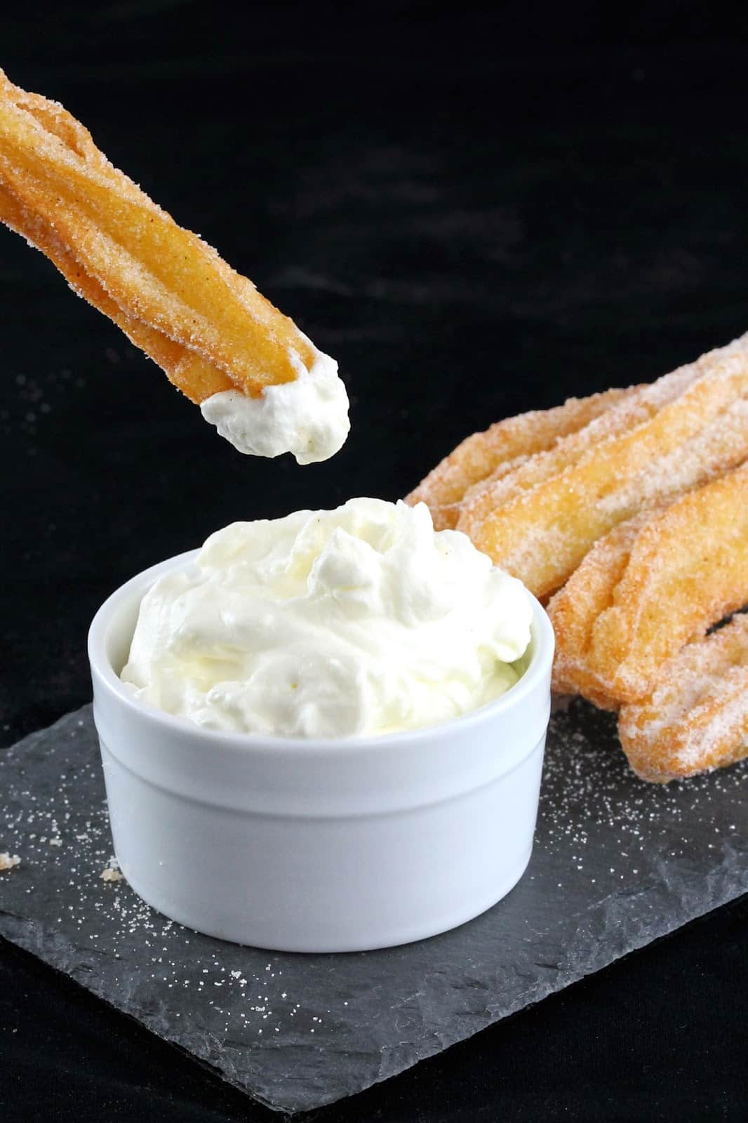 Churro being dipped into cream.