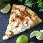 Slice of Cilantro Lime Chicken Pizza on a black countertop surrounded by lime wedges.