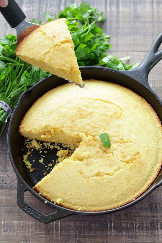 Slice of cornbread being held over skillet full of cornbread with slice removed