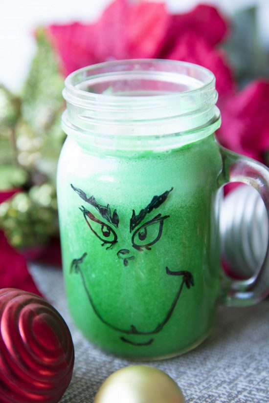 Green grinch punch in a mason jar cup with a handle and a grinch face drawn on it with a marker
