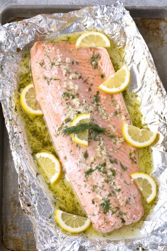Baked salmon recipe pictured from above that includes lemon, butter, dill, and garlic