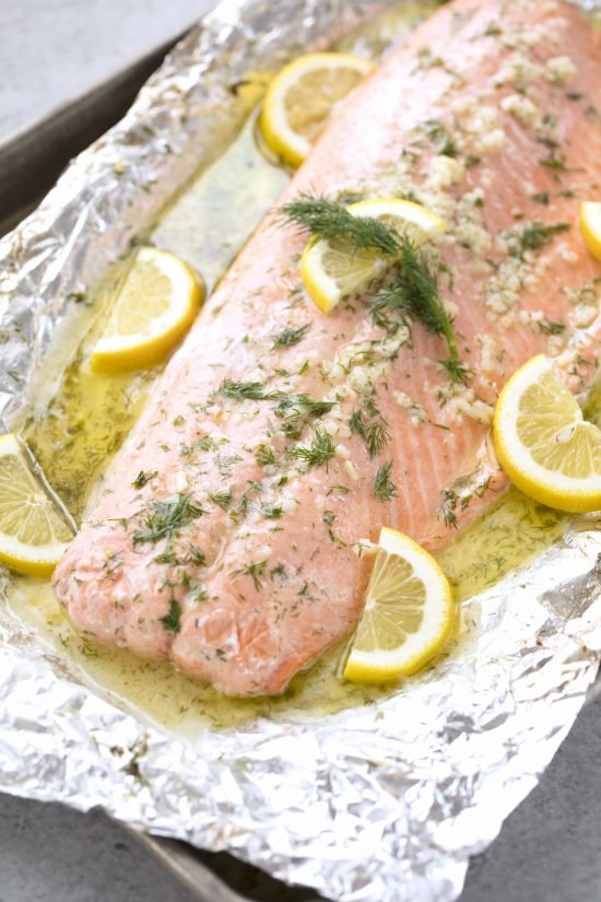 Baked salmon with lemon slices, garlic, and dill sitting in tin foil with all the juices