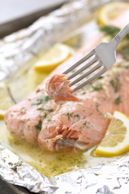 Piece of baked salmon on a fork with large filet of salmon in the background