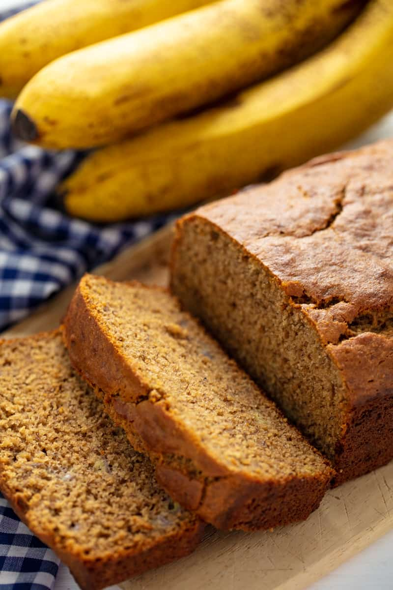 Banana Bread with two slices taken off the end, laying on each other all on a cutting board.