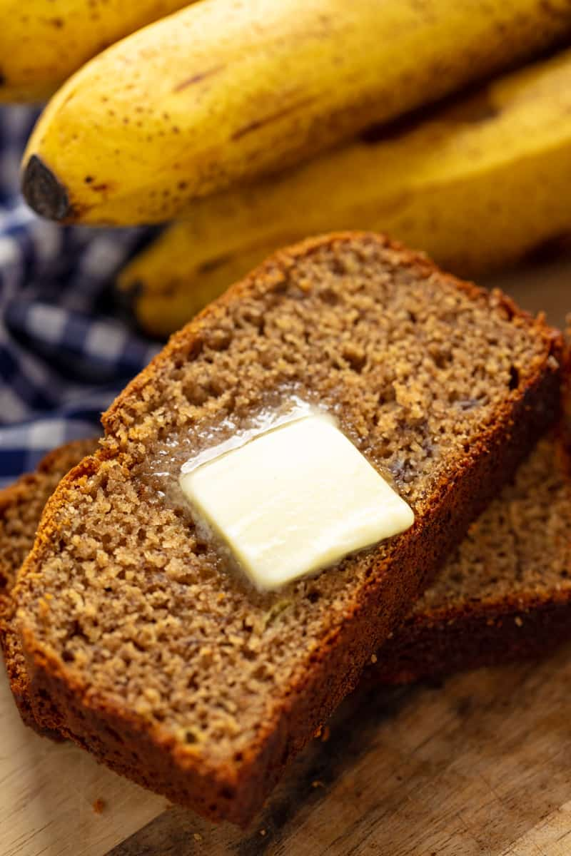 A slice of Banana Bread with a pad of butter melting on it.