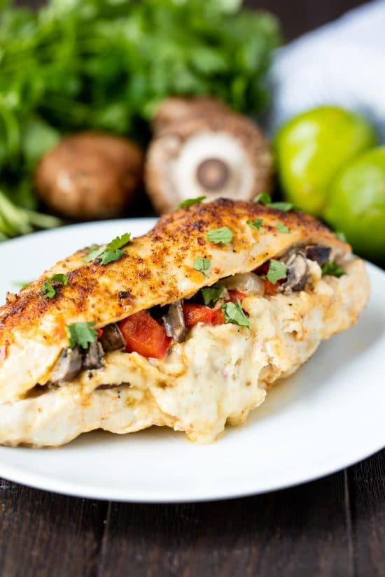 Fajita stuffed chicken breast on a white plate with mushrooms, peppers, and cheese