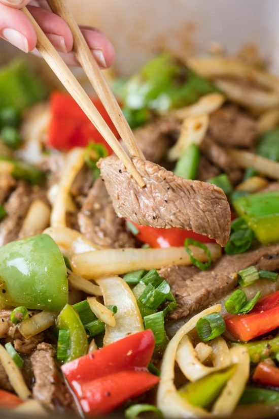 Chopsticks holding a slice of easy Chinese pepper steak over a wok full of stir fry