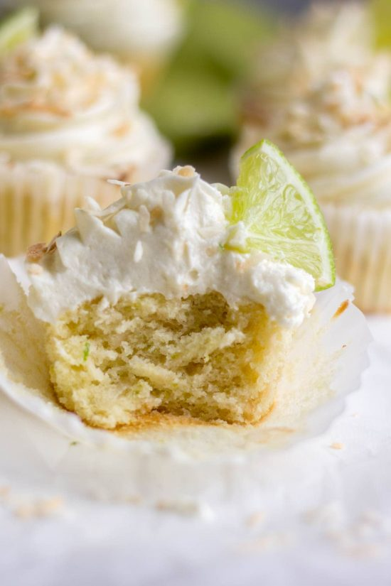 Coconut lime cupcake topped with toasted coconut, and a quarter slice of lime with a bite out of it