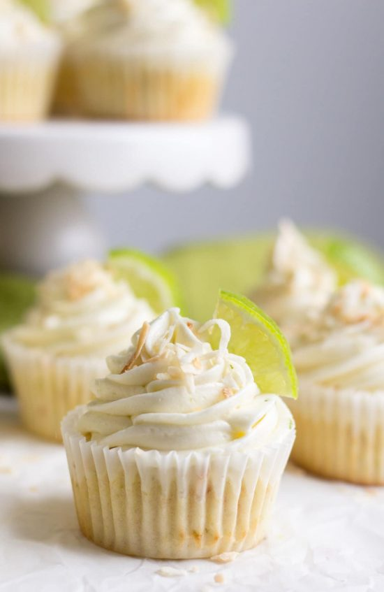 Coconut lime cupcake topped with toasted coconut, and a quarter slice of lime