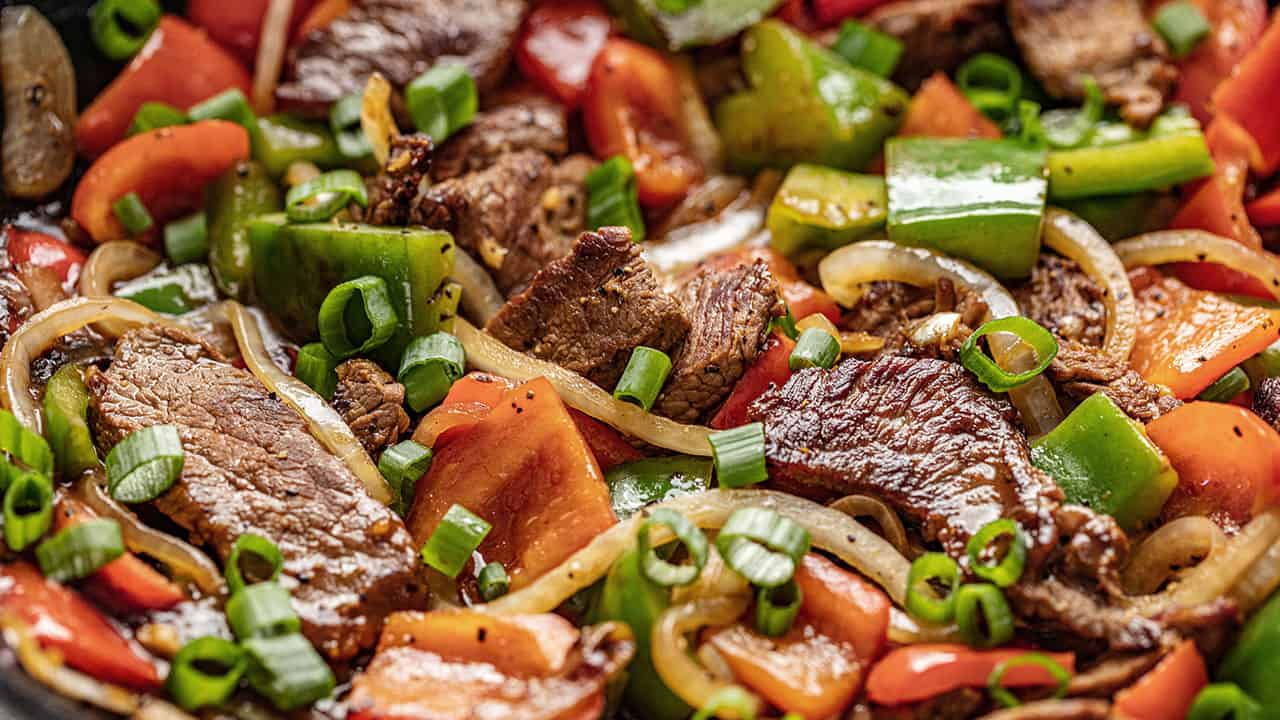 Closeup of Easy Chinese Pepper Steak with red and green peppers, white onion and chopped green onion