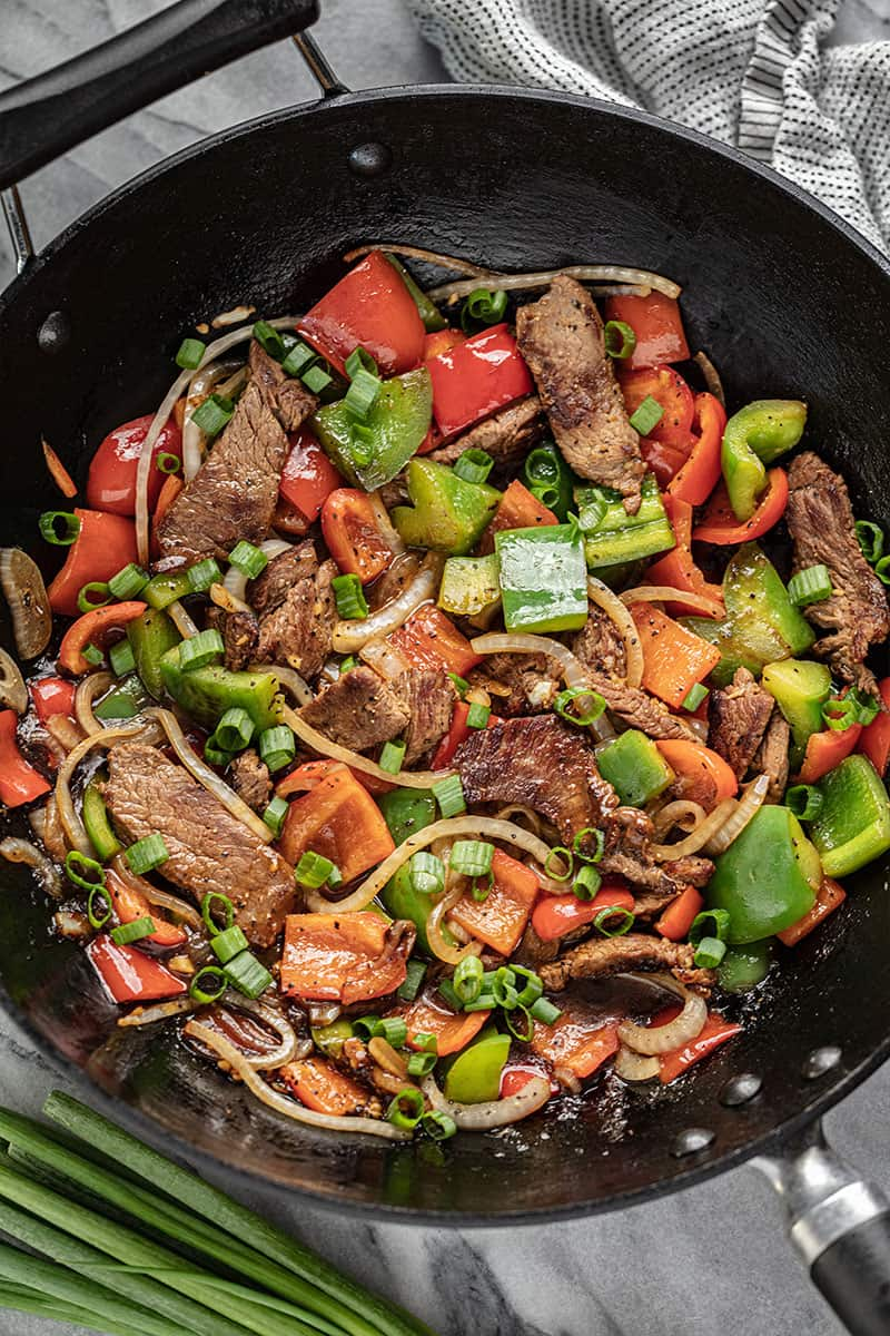Easy Chinese Pepper Steak in a skillet with steak, red and green peppers, white onion and chopped green onion