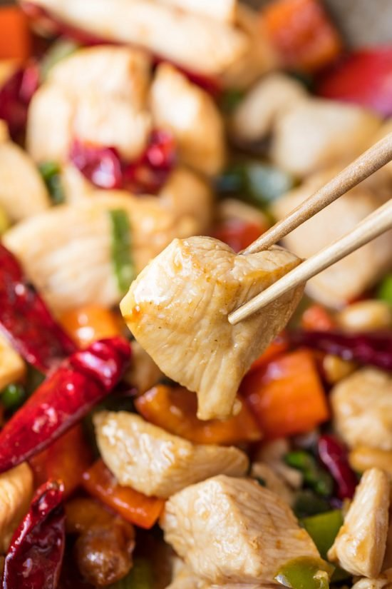 Chopsticks holding a piece of Kung Pao chicken over a bowl full of Kung Pao chicken