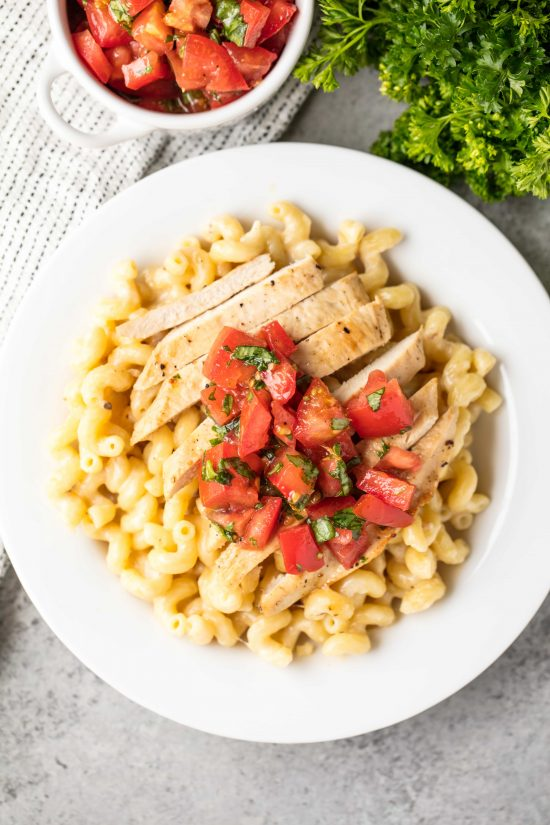3 cheese chicken cavatappi topped with grilled chicken and a tomato bruschetta