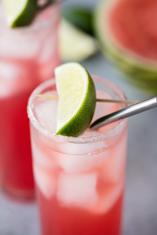 Key west cooler mocktail in a slender glass cup, lip lined with sour sugar and an a lime slice on top