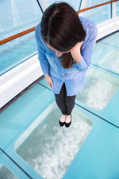 Woman looking through glass floor to ocean below on top level of cruise ship